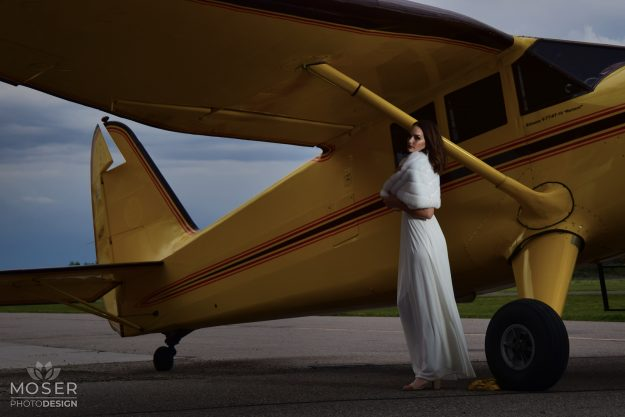 Woman in white in front of a yellow plane