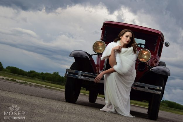 Woman in white on the front of an old car